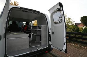 Einblick in den Microcamper durch die geöffneten Hecktüren. Auch die Türen sind mit grauem Stoff verkleidet. Stimmig dazu der grau gesprenkelte Fußboden. Die Dachverkleidung ist weiß, für einen hellen Innenraum.