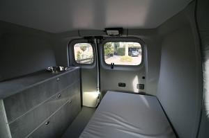 Innenansicht eines ausgestatteten Microcampers Nissan NV 200 mit Küchenblock, ausziehbarer Sitzbank / Schlafbank, Fußboden und Wandverkleidung.